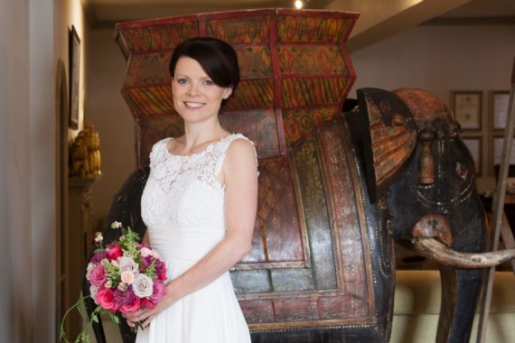 Bride posing in front of elephant at Elephant Hotel Pangbourne