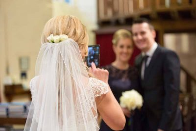 The bride taking photos in the church! Natural wedding photography Oxfordshire