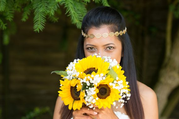 Bride peeping over sunflower bouquet