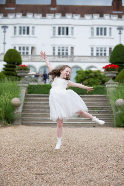 Young bridesmaid dancing at Danesfield House