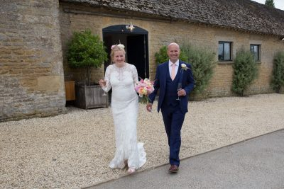 Bride and Groom walking in front of Merriscourt Barn, Cotswolds