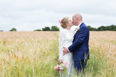 Bride and Groom kissing in field at Merriscourt Barn Wedding, Cotswolds