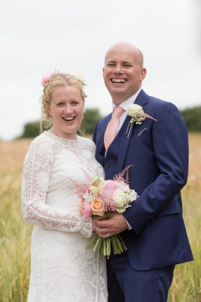 Happy Bride and Groom in field at Merriscourt in Cotswolds