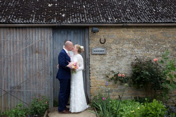 A kiss at wedding at Merriscourt Barn Cotswolds Oxfordshire