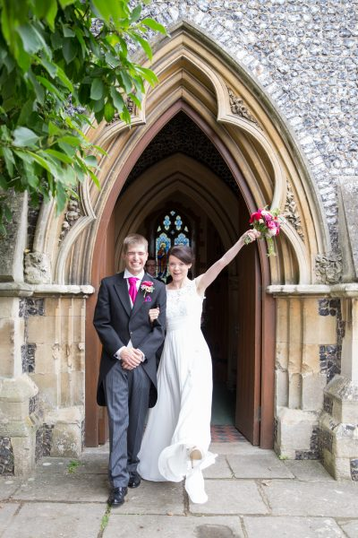 Happy couple come out of church after wedding in Pangbourne Berkshire