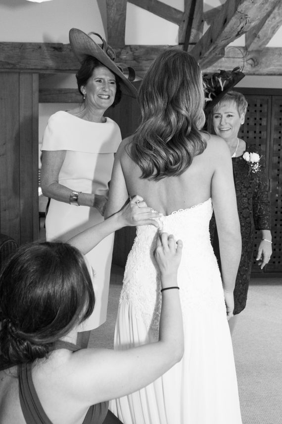 Wasing Park Berkshire wedding - adjusting the bride's dress