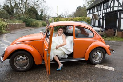 Bride arriving at her wedding in orange VW Beetle in Bix Henley
