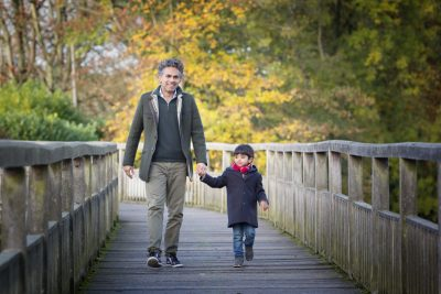 Father and son walking along the river at Henley