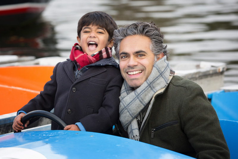Father and son playing in boat at Henley