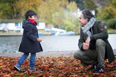 Father and son playing in leaves at Henley