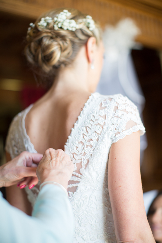 Mother helping daughter into her wedding dress at Stoke Park