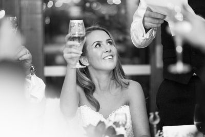 Bride holding up champagne at Wasing Park Wedding