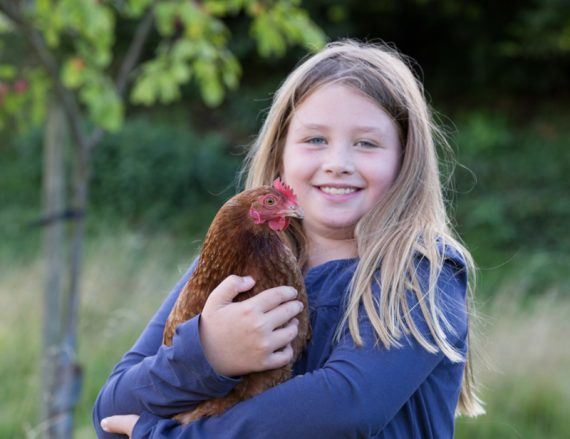 young girl with chicken in family shoot