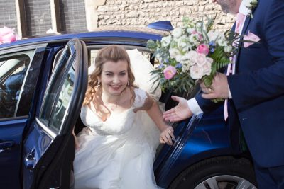 Bride emerging from car at her Abingdon wedding