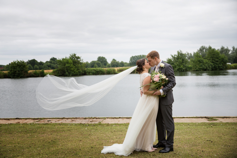 Bride and Groom kissing by the river at Shiplake College Wedding