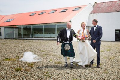 Laughing bride as her veil blows off at Crear Wedding