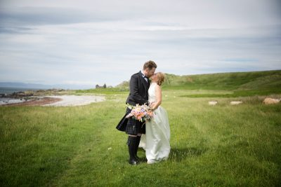 Bride and Groom kissing on the beach at their Crear Wedding
