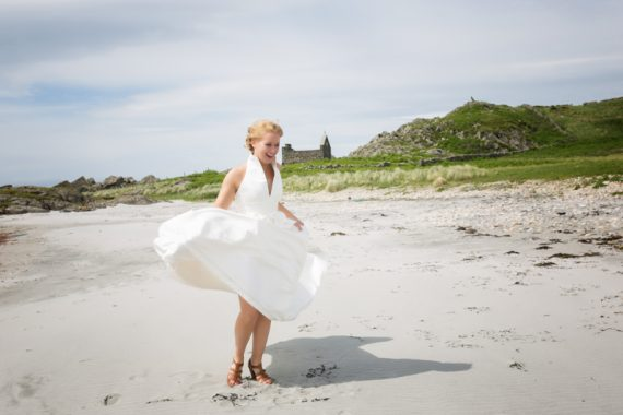 Wind blowing up bride's dress on beach at Crear in Scotland