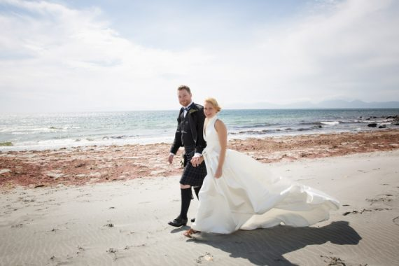 Bride and Groom hand in hand on beach at Crear