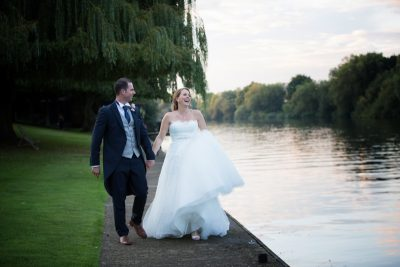 Bride and Groom walking along river at Oakley Court Wedding