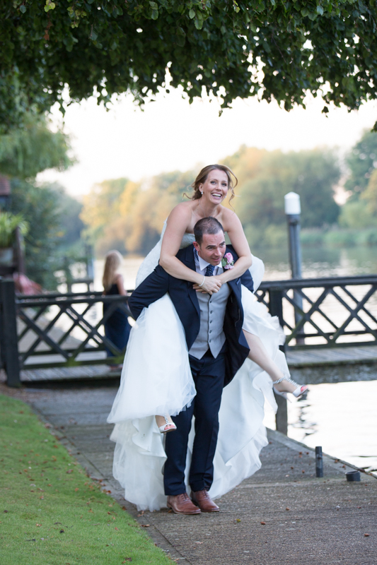 Groom giving his bride a piggy back at their Oakley Court Wedding in Berkshire