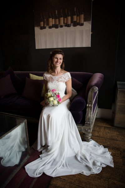 Bride sitting on sofa at reception in Hotel du Vin in Henley