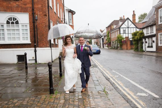 Bride and Groom walking in the rain near Hotel du Vin in Henley