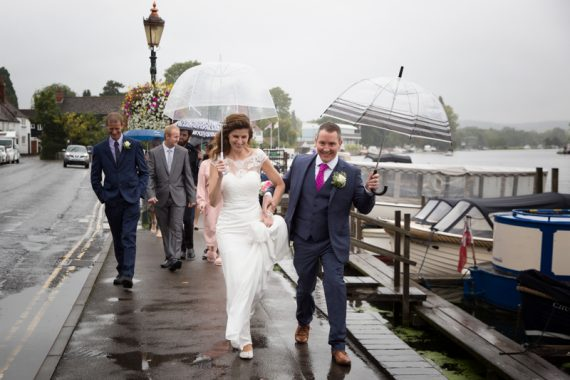 Bride and Groom walking near river in Henley in the rain