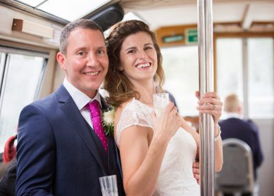 Bride and Groom smiling at the camera on a boat party on the Thames