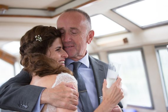 Bride in embrace at her wedding party on boat in the Thames