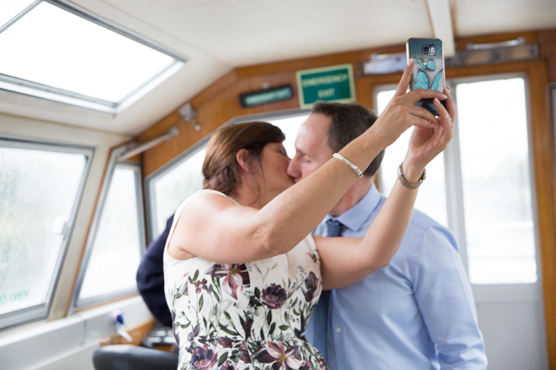 Couple kissing at a wedding party on boat in Henley