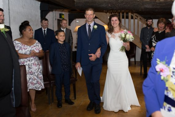 Bride and her brother walking down the aisle at Hotel du Vin wedding in Henley