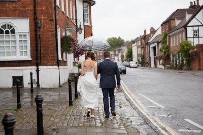 Couple walking in the rain after their wedding at Hotel du Vin Henley