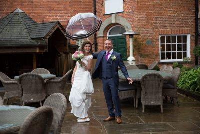 Bride and Groom with umbrella in rain at Hotel du Vin Hotel