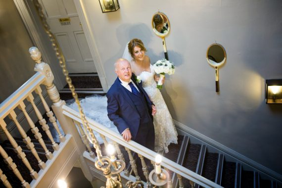 Bride and her Father on the stairs at the olde bell hotel in Hurley
