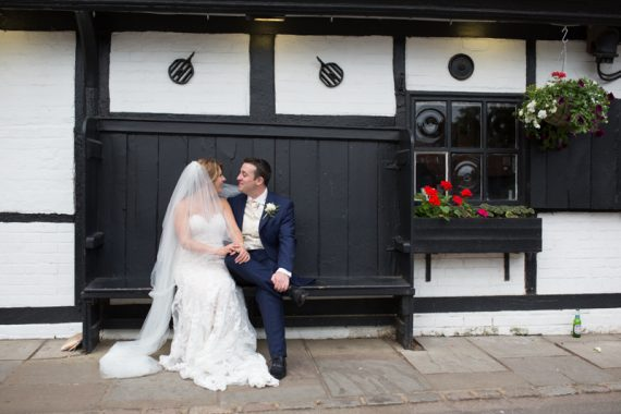 Bride and Groom sitting outside the Olde Bell Hotel in Hurley