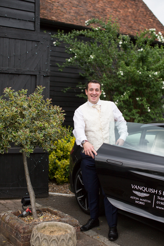 Groom getting out of sports car at his wedding in Hurley