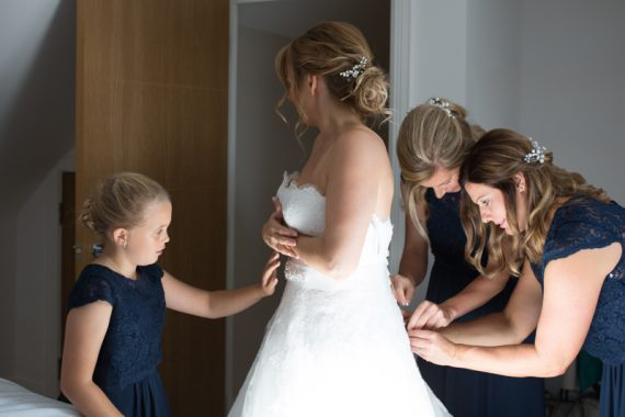 Bride with her bridesmaids getting into her dress