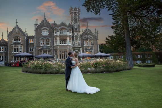 Bride and Groom kissing at sunset at Oakley Court Wedding