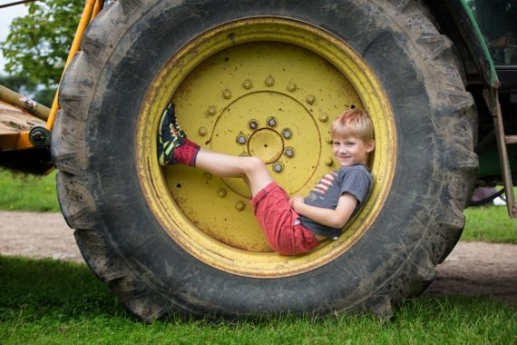 Boy sitting in wheel of tractor in family photo shoot near Henley