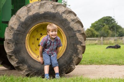 Boy smiling in wheel of tractor Henley