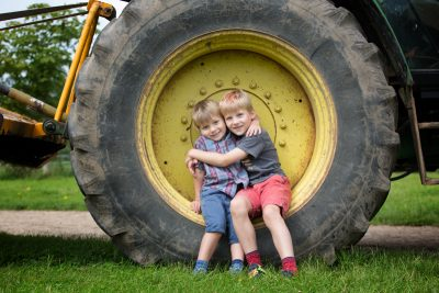 Boys in wheel of tractor in family photo shoot in Henley