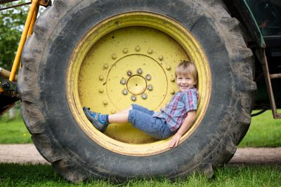 Boy smiling in tractor wheel in family portrait session Henley