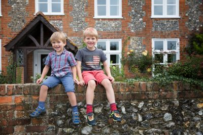 Informal and fun portrait of boys sitting on a wall near Henley