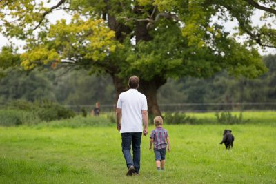 Portrait of father and son walking in countryside near Henle