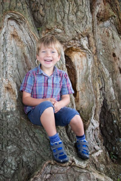 Young boy looking happy on tree near Henley on Thames