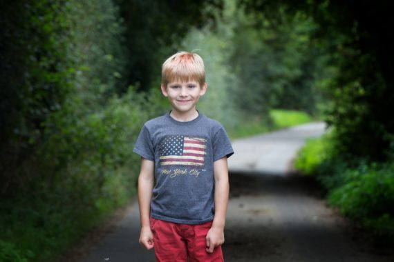 Boy standing in country road in informal family portrait sesion
