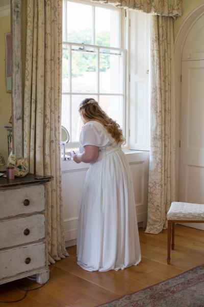 Bride putting on her make up at Rockley Manor