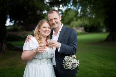 Couple toasting their wedding in the gardens at Rockley Manor