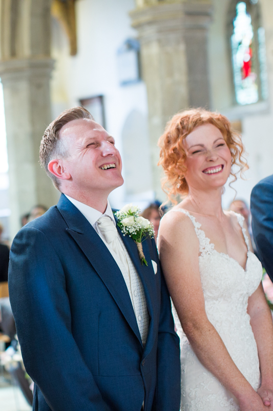 Bride and Groom laughing at St Michel's church in Warfield